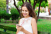 A pretty girl in a white dress is listening to her favourite song on the bench in the park. She enjoys and is having fun