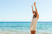 Portrair of young woman dressed in a white dress and a brown hat standing at the beach and putting hads up. Girl is engoying her freedom and fresh air. Feel free concept