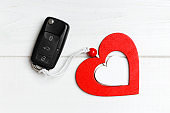 Top view of car key and heart as a present for Valentine's day on wooden background. Romance concept