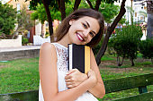 Beautiful girl is sitting on the bench in the park and hugging a book