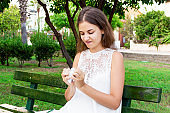 An angry girl is sitting on the bench in the park holding crumpled paper, a pen and a notebook