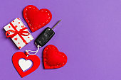 Top view of car key, gift boxes and toy hearts on colorful background. Saint Valentine's Day concept with copy space