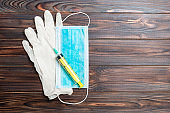 Top view of disposable surgical mask, pair of latex medical gloves and syringe on wooden background. Protect your health concept with copy space
