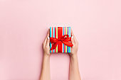 Female's hands holding striped gift box with colored ribbon on living coral background. Christmas concept or other holiday handmade present box, concept top view with copy space