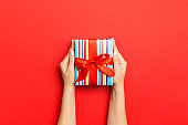 Female's hands holding striped gift box with colored ribbon on red background. Christmas concept or other holiday handmade present box, concept top view with copy space