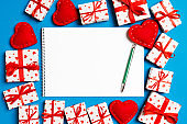 Top view of notebook surrounded with gift boxes and hearts on colorful background. Valentine's Day concept