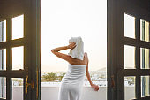 Back view of pretty girl on a balcony wrapped in white towel after having a bath. Woman is enjoying a mountain view and the sunset. Spa concept