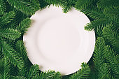 Top view of white plate surrounded with fir tree branches. Christmas dinner concept with copy space