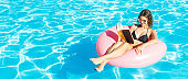Young woman is reading a book sitting on the inflatable ring in the swimming pool. Summer relaxation concept