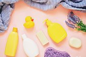 Top view photography baby care cosmetics with natural herbal extracts. Yellow shampoo bottle, soap bar, shower gel and rubber duck. Organic bath products