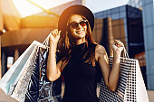 Happy attractive elegant girl, in a black dress and hat, wearing dark glasses, holding shopping bags and enjoying shopping. Black Friday