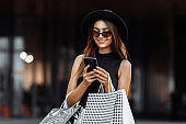 Happy beautiful elegant girl in a black dress and hat, using a mobile phone, holding shopping bags. Black Friday, shopping