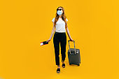 A female passenger in a medical protective mask on her face, with a suitcase and passport, goes abroad. Concept of travel, quarantine and coronavirus