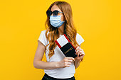 A girl passenger in a medical protective mask on her face, with a passport and tickets, goes abroad. Concept of travel, quarantine and coronavirus