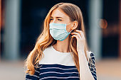 young attractive young woman in a medical protective mask on her face, standing in the city against the background of a building. Quarantine, coronavirus,