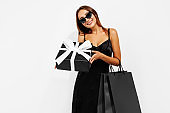 Elegant young woman in black dress and sunglasses standing on white background with shopping bags and gift, Black Friday concept, shopping