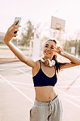 Happy fitness girl with headphones taking selfie outdoors while doing sports