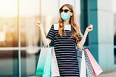 Close-up of a stylish, beautiful young woman in sunglasses and a medical protective mask on her face, carrying shopping bags, leaving a shopping center after shopping. Quarantine, coronavirus