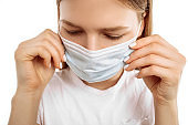 Young woman using medical protective mask to protect health and prevent virus, epidemic and infectious diseases, on white background