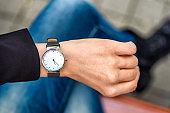 What time is it. Silver wristwatch on hand of woman.