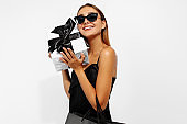 Excited happy young woman in sunglasses, in elegant black dress with shopping bags and a gift on a white background, Concept of holiday, shopping, Black Friday