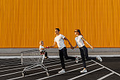 Happy family makes purchases, husband and wife with a child have fun and run around with a shopping cart, against the background of a yellow wall of a shopping center
