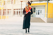 A graduate student in a medical mask, in a black graduation dress, with a diploma in her hands. Graduation ceremony concept, quarantine, coronavirus