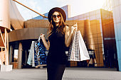 attractive elegant girl, in a black dress and hat, wearing dark glasses, holding shopping bags and enjoying shopping. Black Friday