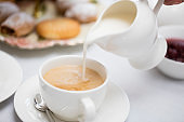 Pouring Milk on Hot English Tea in a White Teacup