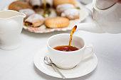 Pouring hot English tea into white ceramic tea cup