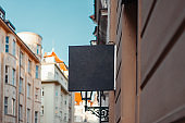 Blank Foursquare Antique Black Store Signboard Mock up on Ancient Wall in European Town. Front View.