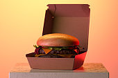 Cheeseburger in Box From Recyclable Craft Paper Or Cardboard Illuminated By Warm Light. Delivery. 3d rendering