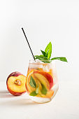 Detox peach lemonade in glass garnish mint. Close up.