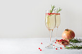 Sparkling wine, pomegranate, rosemary sprig on white table. Xmas drink.