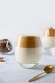 Two glasses of Korean Dalgona coffee on white on white background. Vertical shot.