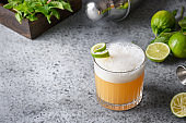 Pisco sour cocktail - whiskey with lime juice, sugar syrup and egg white. Close up.