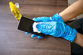 Woman's hand in blue gloves sanitizing cleaning smartphone mobile phone with alcohol on wood table surface with wet wipes
