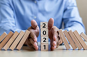 Businessman hand Stopping Falling of 2021 wooden Blocks. Business, Risk Management, Insurance, Resolution, strategy, solution, goal, New Year New You and happy holiday concepts