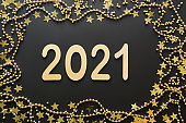 Christmas creative shiny border of golden date and beads on black background with date 2021 New Year.