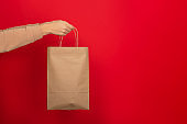 Female hand hold large gift bag made of brown craft paper on red background