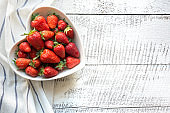 Ripe organic strawberry in plate as heart on white wooden background. Top view.