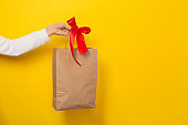 Female hand hold large gift bag made of brown craft paper with a red bow.