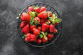 Ripe organic strawberry on dark background. Top view.