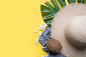 Beach straw sun hat, coconuts, seashell and monstera leaves. Summer holiday background with accessories. Top view.