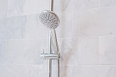Water drops spraying or running from shower head and faucet with marble wall background in modern bathroom
