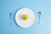 Top view spoon and fork, green apple on white ceramic plate on blue background. dieting, weight loss, obesity and food control concept