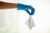Throw a damp wet wipe into the trash, hand in blue protective glove