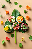 Puffed rice cakes with different toppings friuts and vegetables on white. Vegan snacks. Vertical format.