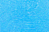 Blue floor mosaic tiles of swimming pool, water surface with ripple. Texture or background.