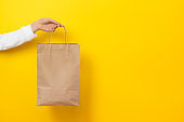 Female hand hold large gift bag made of brown craft paper on yellow background